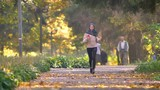 Muslim woman in hijab with earphones goes jogging in autumnal park with people on background - 237236378