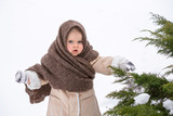 Little Caucasian girl for 2 years on a white background. The girl of nursery age in the winter is on the snow, dressed in a sheepskin coat, a warm scarf, boots and mittens. The child looks forward. - 237236580