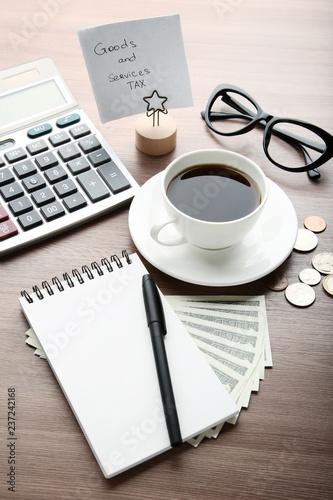 Inscription Goods and Services Tax with cup of coffee, notebook, calculator and banknotes - 237242168