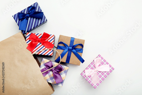 Leinwandbild Motiv Shopping bag with gift boxes on grey background