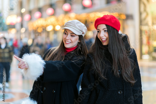 fototapeta na ścianę Two attractive smiling young women are shopping in the city