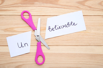 Paper with word Unbelievable and scissors on wooden table