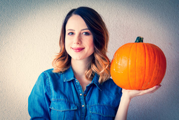 Redhead woman in jeans clothes holding orange autumn pumpkin. Portrait on white background
