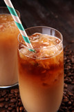 Ice coffee on a rustic table with cream being poured into it showing the texture and refreshing look of the drink