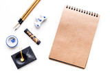 Lesson of calligraphy concept. blank sheet for lettering near writing accessories on white background top view mockup