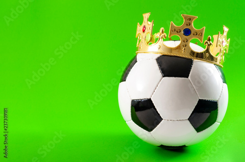 Football is the king of sports, championship winner and league champion concept with a soccer ball wearing a golden crown isolated on green background with copy space - 237309181