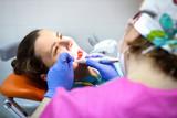 Dentist treats patient's teeth in dental clinic.