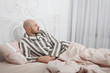 Quadro Handsome bald, bearded man in striped pajamas is lying and thinking in bed with pillows and pink bedding.