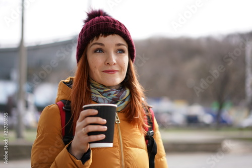 woman on a street with cup of tea