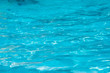 Blue and bright water surface and ripple wave with sun reflection in swimming pool