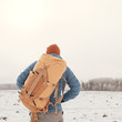 Leinwanddruck Bild - back view of  tourist with  backpack hiking in winter in Norway / one man carrying  backpack in a Norwegian winter landscape.
