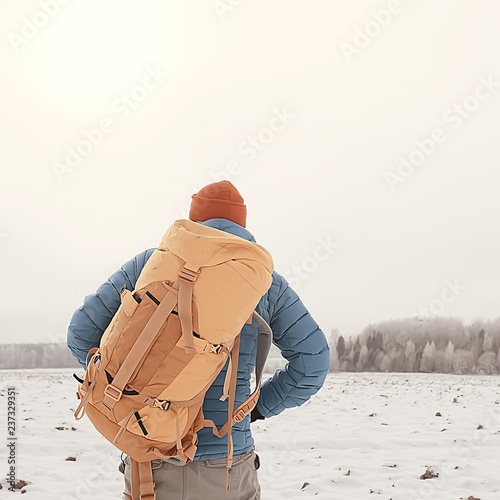 Leinwanddruck Bild back view of  tourist with  backpack hiking in winter in Norway / one man carrying  backpack in a Norwegian winter landscape.