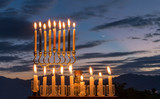 Menorah with burning candles is traditional symbol for Hebrew Holidays and celebration of Hanukkah. Background of night or dawn sky, selective focus on attributes of the Holiday