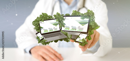 Doctor holding a Connected devices surrounding by leaves 3d rendering