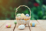 Colorful easter eggs in basket on wooden table win copy space. - 237343745
