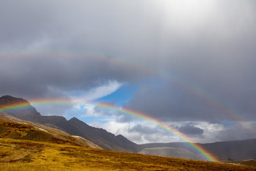 A look from Iceland, when rain falls, a rainbow forms. In the background is the volcanic mountain range.