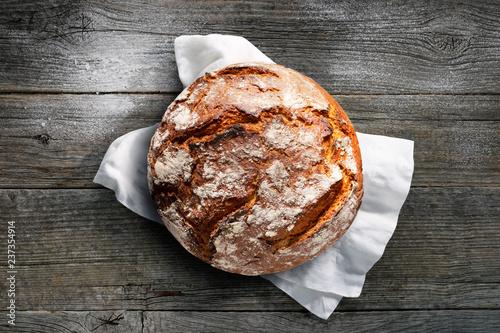 Rustikales Brot auf weißem Tuch mit dunklem Holzuntergrund - 237354914