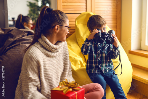 Mother And Son At Living Room Holding Christmas Gift While Sitting In Bean