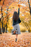 Pretty woman posing with bunch of maple's leaves in autumn park. Beautiful landscape at fall season. - 237366134