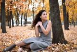 Pretty woman is sitting in autumn park near big tree. Beautiful landscape at fall season. - 237366779