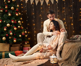 young couple is in christmas decoration and lights, fir tree on dark wooden background, new year holiday concept - 237367130