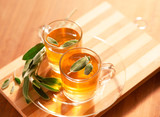 Sage tea infusion with sage leaves on wooden board - 237367366