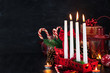 Four Christmas Advent candles and holiday decorations around on dark background