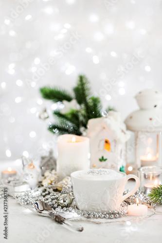 Biała filiżanka gorąca cappuccino kawa na wakacyjnym bielu i srebra tle, Bożenarodzeniowy pojęcie