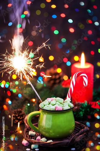 Zielony kubek gorąca czekolada z marshmallows, cukierek trzciną i sparkler na wakacyjnym tle, Bożenarodzeniowy pojęcie