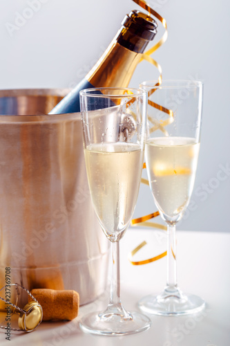 Pair glass of champagne with bottle in metal container. New Year celebration - 237369708
