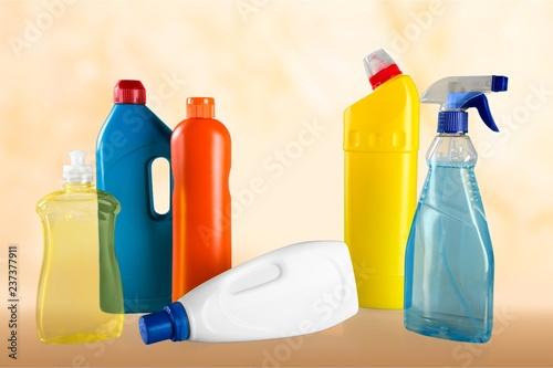Leinwandbild Motiv Plastic bottles, cleaning sponges and gloves on blue background