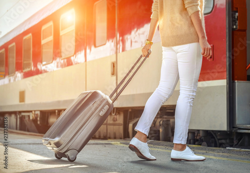 Woman with her luggage go near the red train on the person