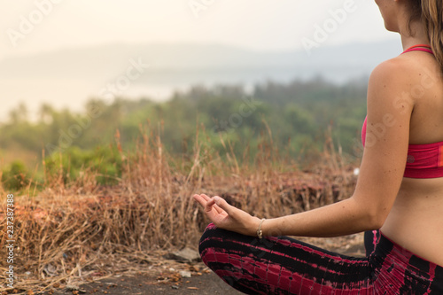 Naklejka Girl sitting and meditating in front of a sunset
