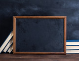 empty black chalk drawing frame and stack of books