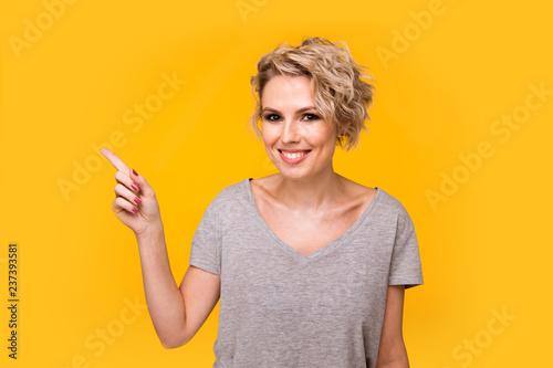 Szczęśliwa zdziwiona blondynki młoda kobieta ono uśmiecha się szeroko przy kamerą, wskazuje palce daleko od, pokazuje coś ciekawy i podniecający na żółtym pracownianym tle z kopii przestrzenią dla twój teksta