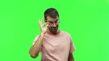 man standing and looking to the front opening the eye with finger  on green screen chroma key background - 237393708