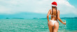 Leinwanddruck Bild - Beautiful  Santa girl in bikini and Christmas hat on the beach of a tropical island, in the hands of a glass of champagne and a red suitcase. Holiday concept for the Christmas holidays and New Year
