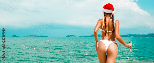 Leinwanddruck Bild Beautiful  Santa girl in bikini and Christmas hat on the beach of a tropical island, in the hands of a glass of champagne and a red suitcase. Holiday concept for the Christmas holidays and New Year