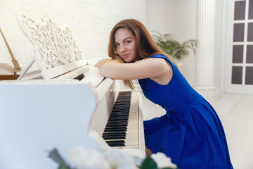 closeup portrait of a girl in blue dress sitting at the piano
