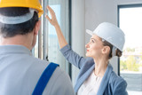 Architect woman and construction worker checking windows on site - 237414750