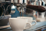 Enjoy barista style coffee. Coffee being brewed in coffeehouse or cafe. Espresso making with portafilter. Coffee cups. Small cups to serve hot drinks. Brewing coffee with espresso machine