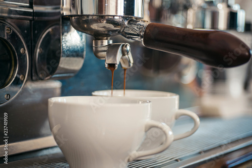Leinwanddruck Bild Enjoy barista style coffee. Coffee being brewed in coffeehouse or cafe. Espresso making with portafilter. Coffee cups. Small cups to serve hot drinks. Brewing coffee with espresso machine