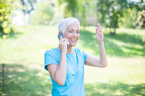 Closeup portrait of sporty senior lady on phone call