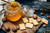 Honey in a jar with wooden honey dipper on a wooden board with crackers, nuts and lavender flowers