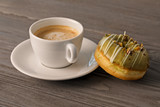 Green doughnut and cup of coffee in the morning light. - 237422992