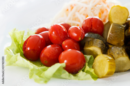 Foto Murales cold appetizer, pickles and tomatoes with sauerkraut laid out on lettuce leaves close-up