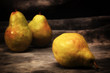 Three ripe pears on gray mottled background, set up, composed and photographed to resemble old fashioned still life painting.