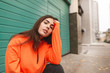 Street portrait of a stylish girl in an orange hoodie, sitting on the street and posing on the camera. Beautiful girl in street clothes sitting on the street.