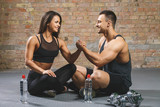 Fitness man and woman giving each other a high five after the training session in gym. Fit couple high five after workout in health club. - 237446538