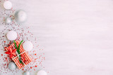Christmas background with confetti, christmas balls, and red gift boxes on the white wooden board - 237451179